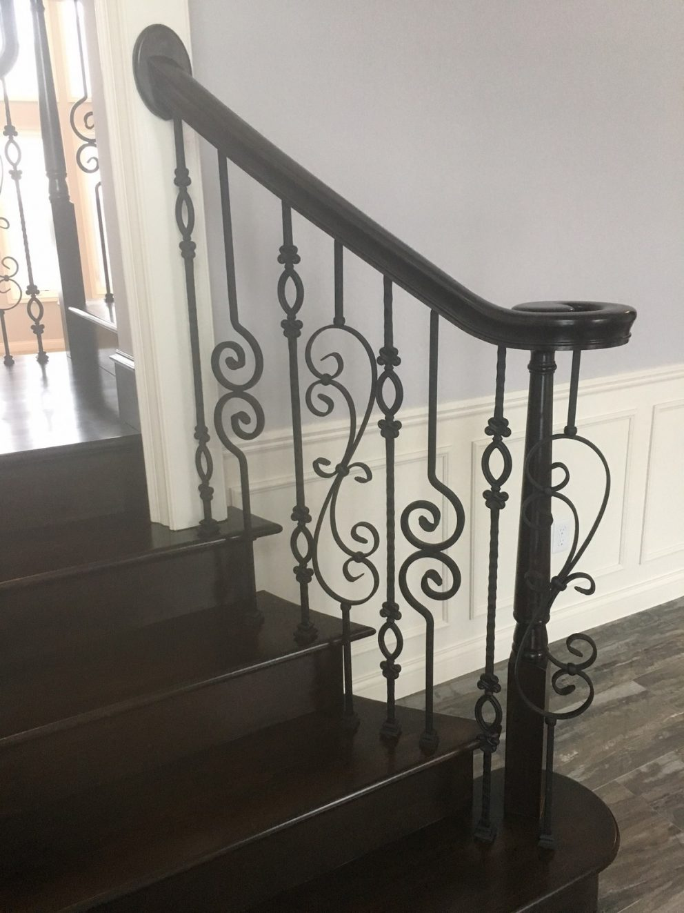 Staircase landing showing off the decorative rod iron spindles and full wood finish