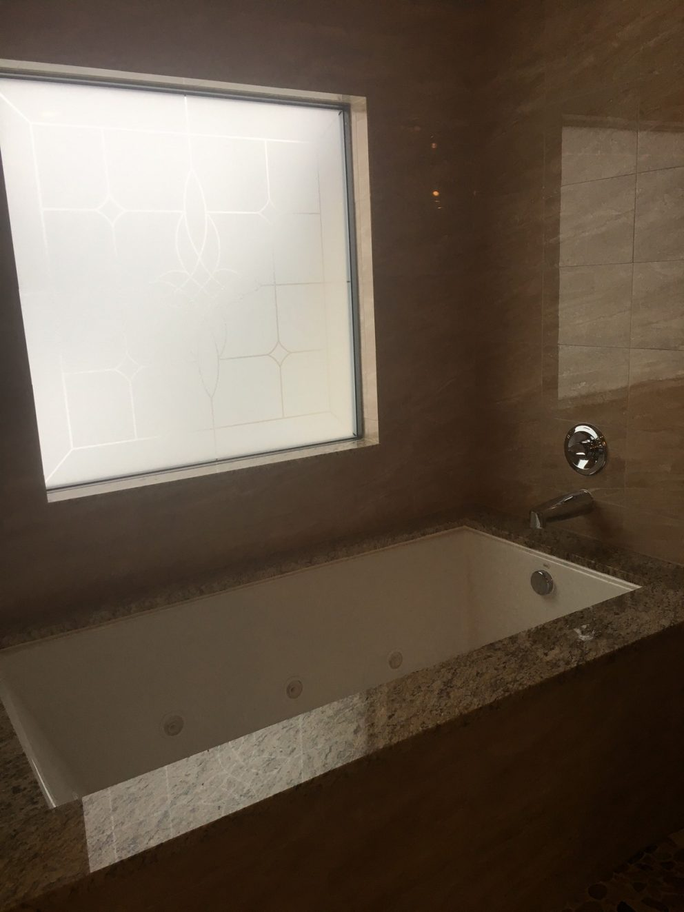 Undermount bathtub in master bath with frosted glass window